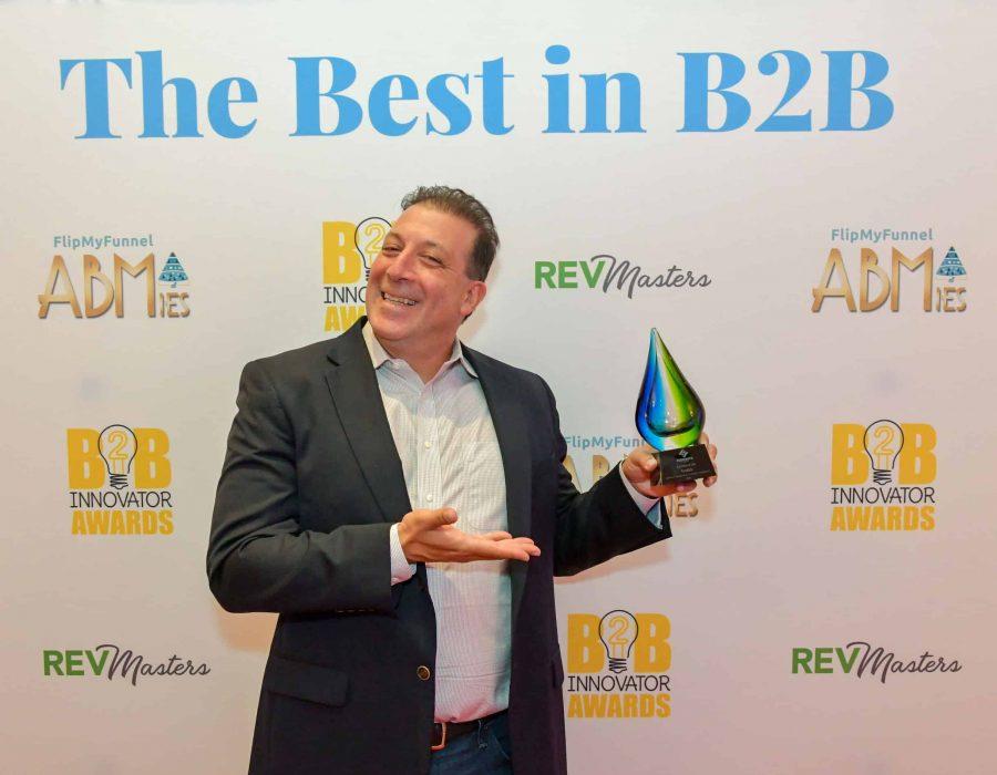 Jeff Pedowitz of The Pedowitz Group proudly displays a REVMasters award.
